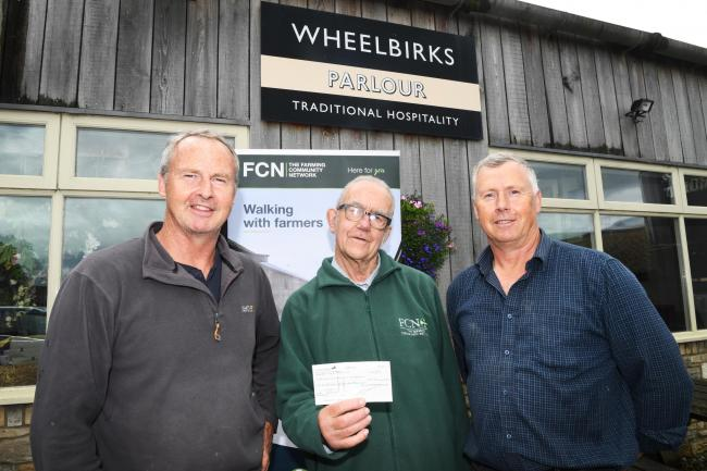 Representing Farming Community Network, Simon Lloyd (centre) collects a cheque from Tom and Hugh Richardson, of Wheelbirks, Stocksfield.
