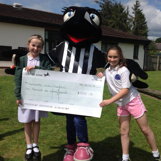 Imogen Nolan (left) and Chloe Makepeace hand over the cheque to Newcastle United mascot Maggie Magpie.