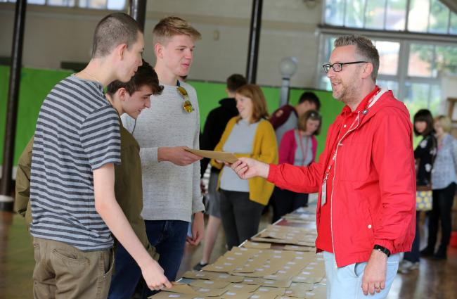 Head of school at Hexham's Queen Elizabeth High School, James Andriot (right), hands out results to pupils.