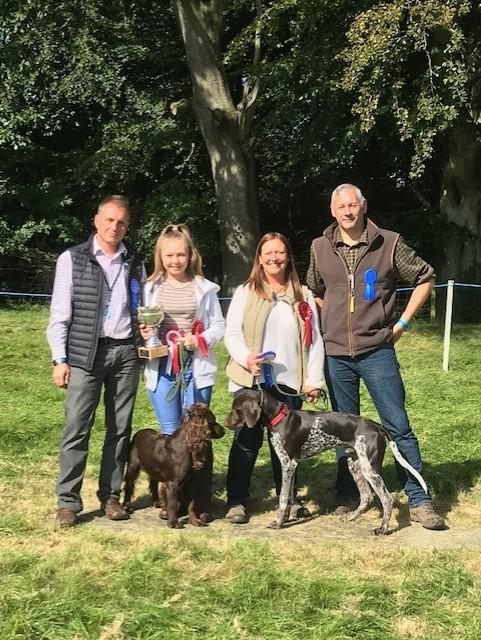 Judges Paul Thompson (left) and John Jackson (right) with dog show winner Reggie and owner Kira Buchanan, and runner-up Talistar with owner Lynn Crozier.