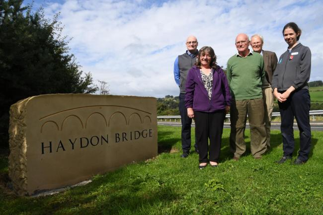 Eileen Charlton, parish council, Mike Atkinson, Haydon Bridge Co-op, Esmond Faulks, parish council, Peter Fletcher, Haydon development trust and Jayne Tulip, Haydon Bridge Co-op next to one of the new village signs. Photo: HX381907. KATE BUCKINGHAM...