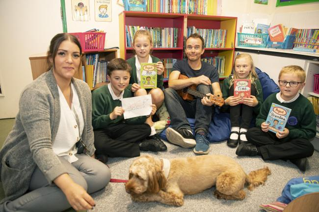 Greenead Primary School head teacher Sarah Hutchinson and students Elias Hershon, Jessica Findlay, Jemimah Donnison and Lennon Heppell with childrens author Gareth Jones and reading dog Hallie. Photo: HX411901. KATE BUCKINGHAM.