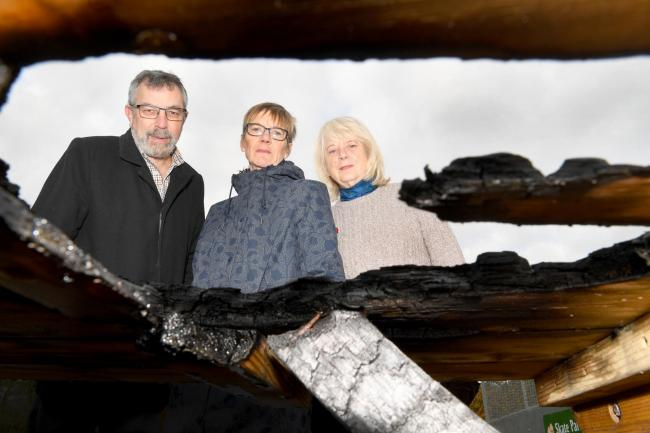 Trustees of Allendale Village Hall, Mike Kirk, Catherine Stirling Hill and Liz Sandison, are pictured through the damage to the picnic table which was found on fire outside the community building. 									             Photo: KATE BUCKINGHAM