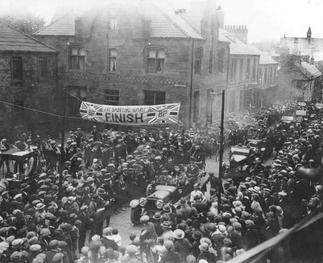 This images shows J.W. Witherspoon winning the Newcastle Exchange 1922 Newcastle to Haltwhistle Walking Race. The latter part of the race went along the Military Road to Greenhead, then back along the now A69, to finish in Haltwhistle Market Place.