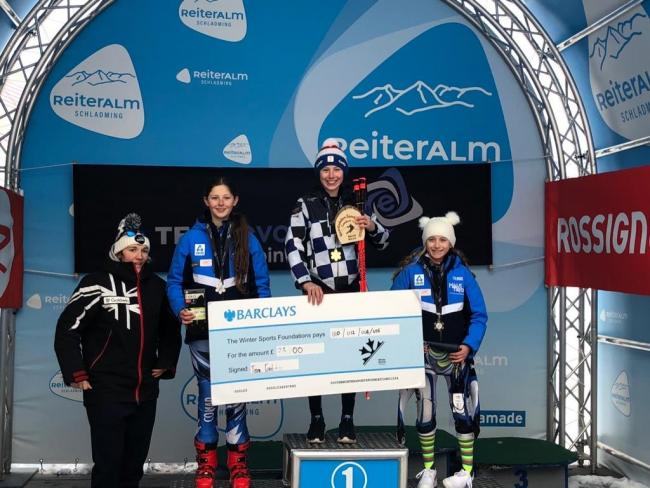 A beaming Hannah Skinner takes first place on the podium in Austria.
