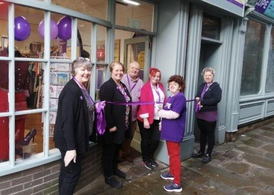 From the left, Hexham's Scope charity shop volunteers Elsie Lowden, Andrea Gaskill, Paul Warren, Sara Berry, Ruth Fish (cutting the ribbon) and Cara Lee Clark celebrate the opening of the new store on Old Church. The charity's previous Fore St
