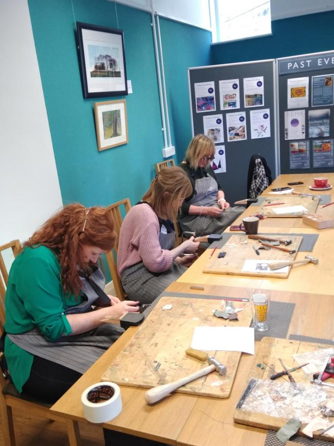 Paricipants work on silver pendants at the Forge in Allendale.
