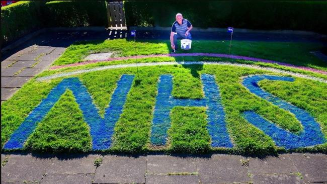 Former greenkeeper John Wilkinson shows off his tribute to the NHS on his lawn.