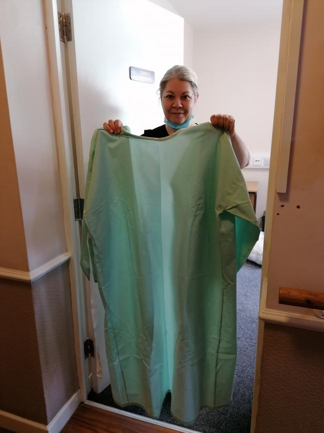 Claudia Ionita, Deputy Manager, holding up one of the completed gowns for Charlotte Straker.