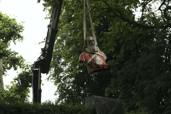 A bust of Belgium's King Leopold II, is hoisted off of its plinth by a crane as it is removed from a park in Ghent, Belgium (Francisco Seco/AP)