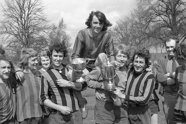 With a little help from Ernie Edwards, Mel Johnson, Joe Worthington Blue Back skipper Bod  Dover, is raised aloft, with the Hexham and District Sunday League Championship Trophy and the President's Cup.