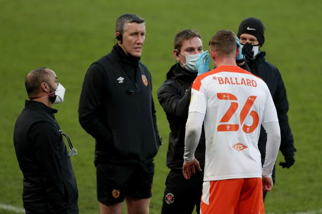 Blackpool's Daniel Ballard gets treatment by masked doctors for a head injury during the Sky Bet League One match at the KCOM Stadium, Hull. PA Photo. Picture date: Saturday January 16, 2021. See PA story SOCCER Hull. Photo credit should read: Richard