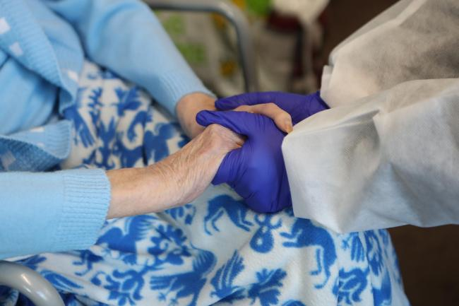 A care home resident holds hands with a friend who has visited (Danny Lawson/PA)