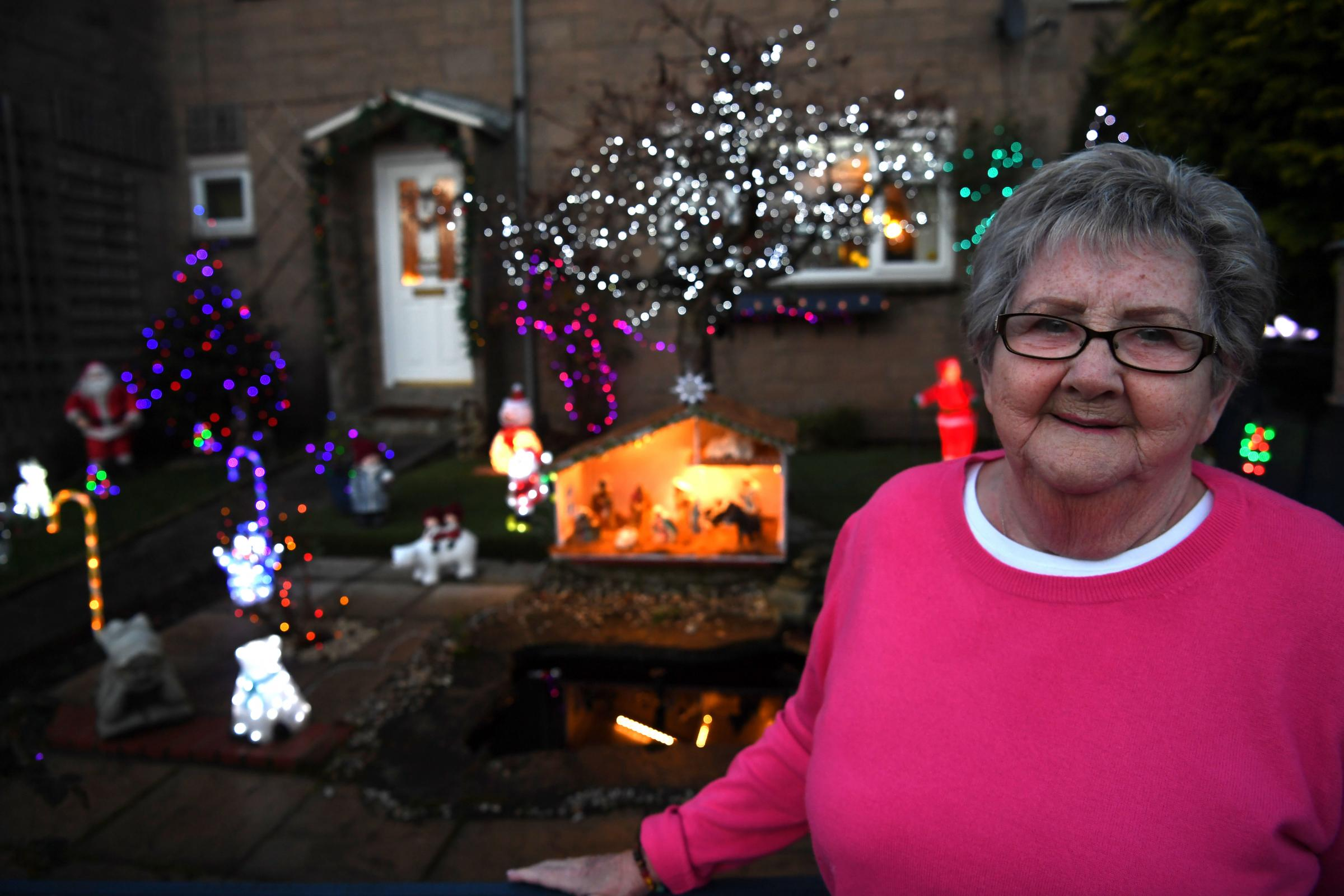 Rosa Buchanan with her an festive lights display outside her house in Bellingham which is raising money for Tynedale Hospice at Home. 								     Photo: KATE BUCKINGHAM