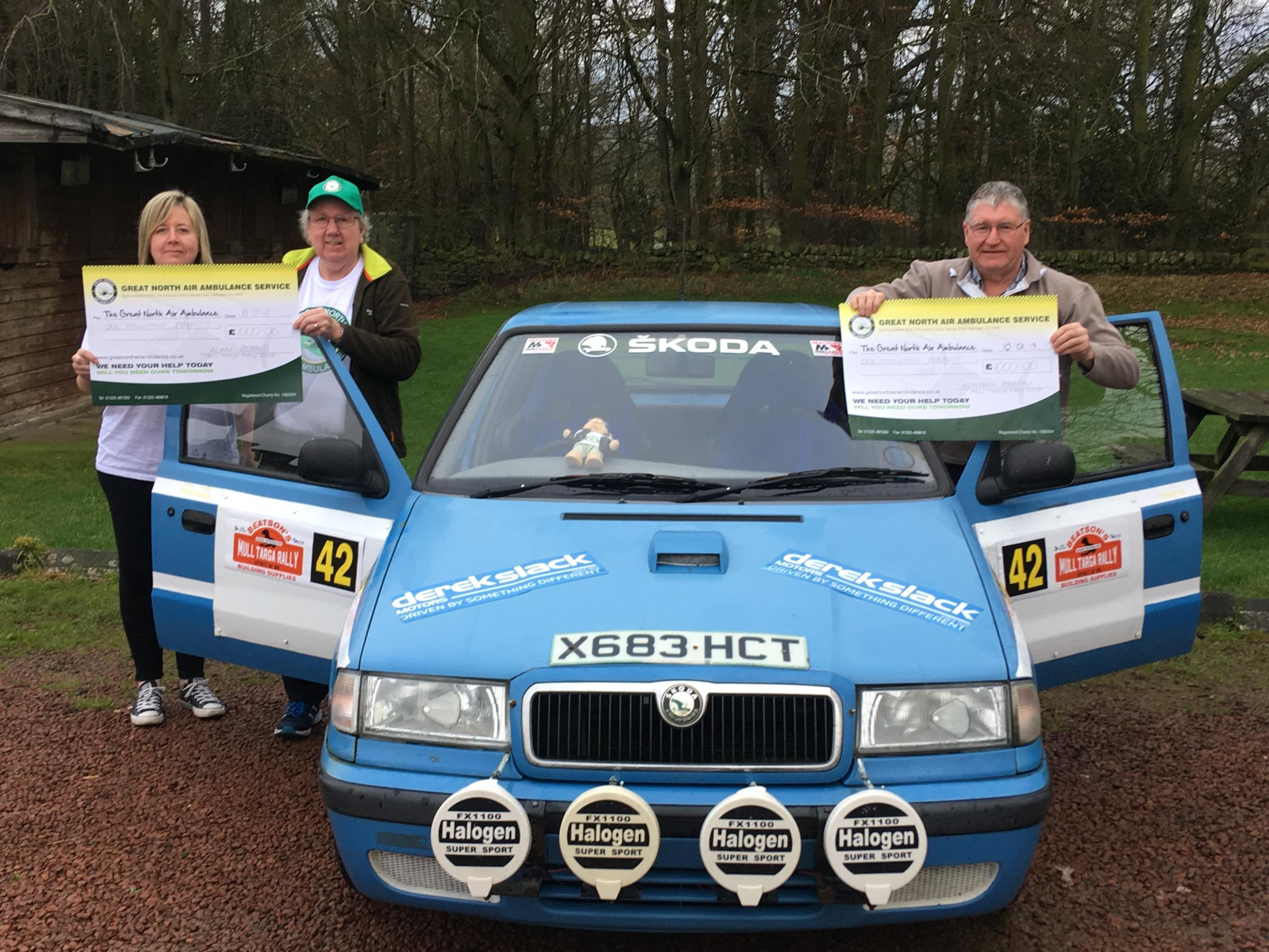 Debbie Gibbs from the Great North Air Ambulance Service receives a cheque from Alan Bland (left) and his co-driver Alistair Murray.