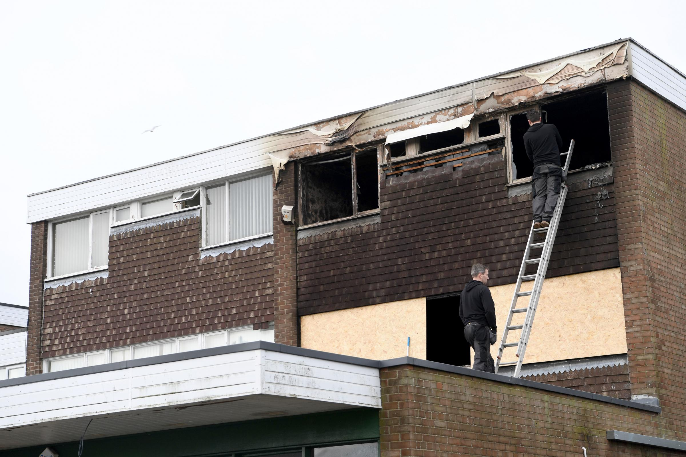 Work is carried out to board up the burnt-out flat at Broadway, in Darras Hall.     Photo: KATE BUCKINGHAM