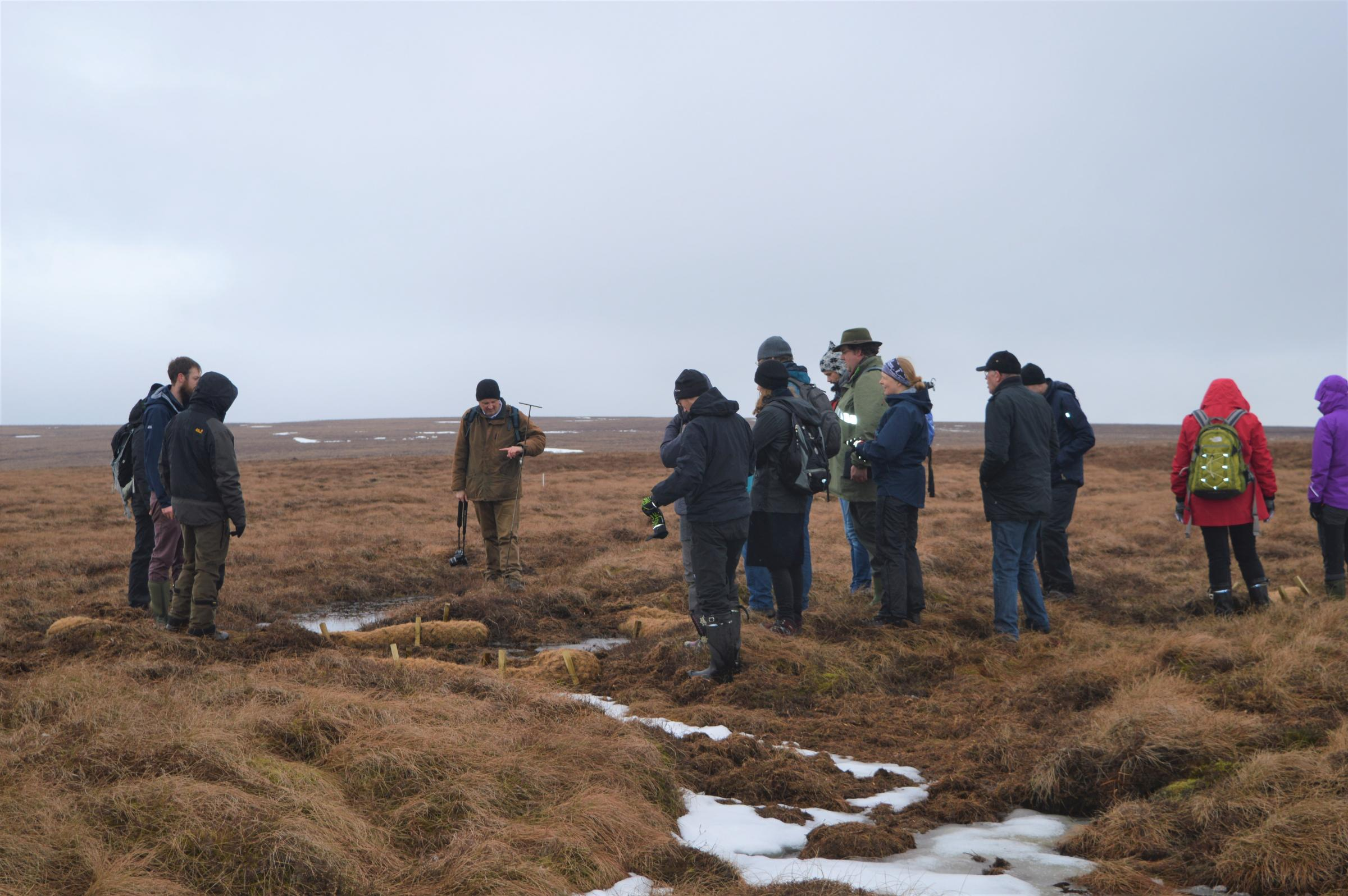 Paul Leadbitter, peatland programme manager for the North Pennines AONB Partnership, demonstrates restoration techniques to international visitors in 2018.