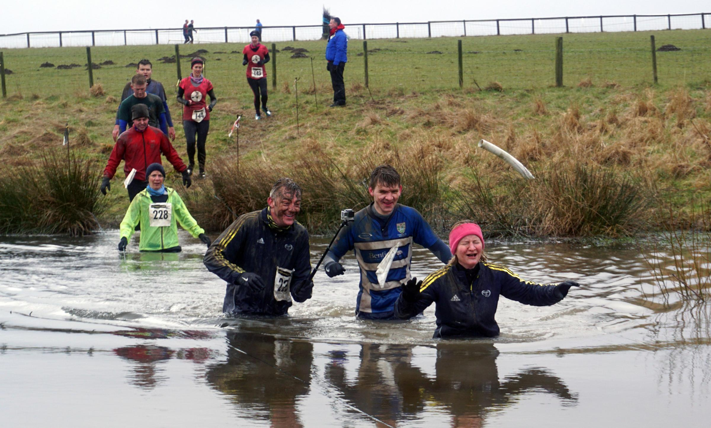 Participants in the 2016 Mad March Mare wade through the ice cold lake at Hexham Racecourse. 						    Photo: www.thecameracowboy.com