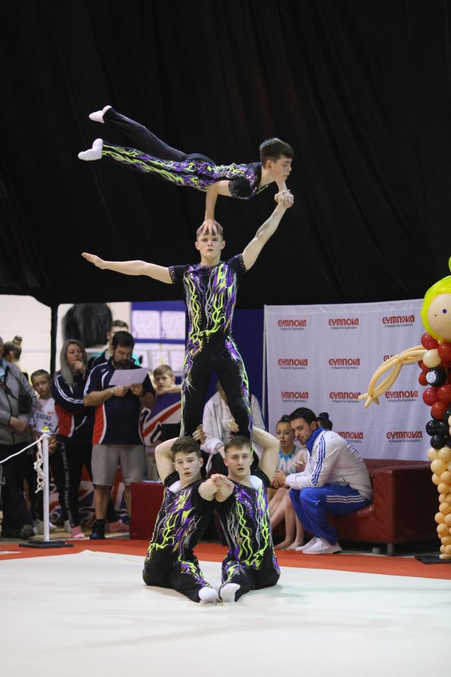 Acro gymnast Jonny Henderson (top) with his teammates.
