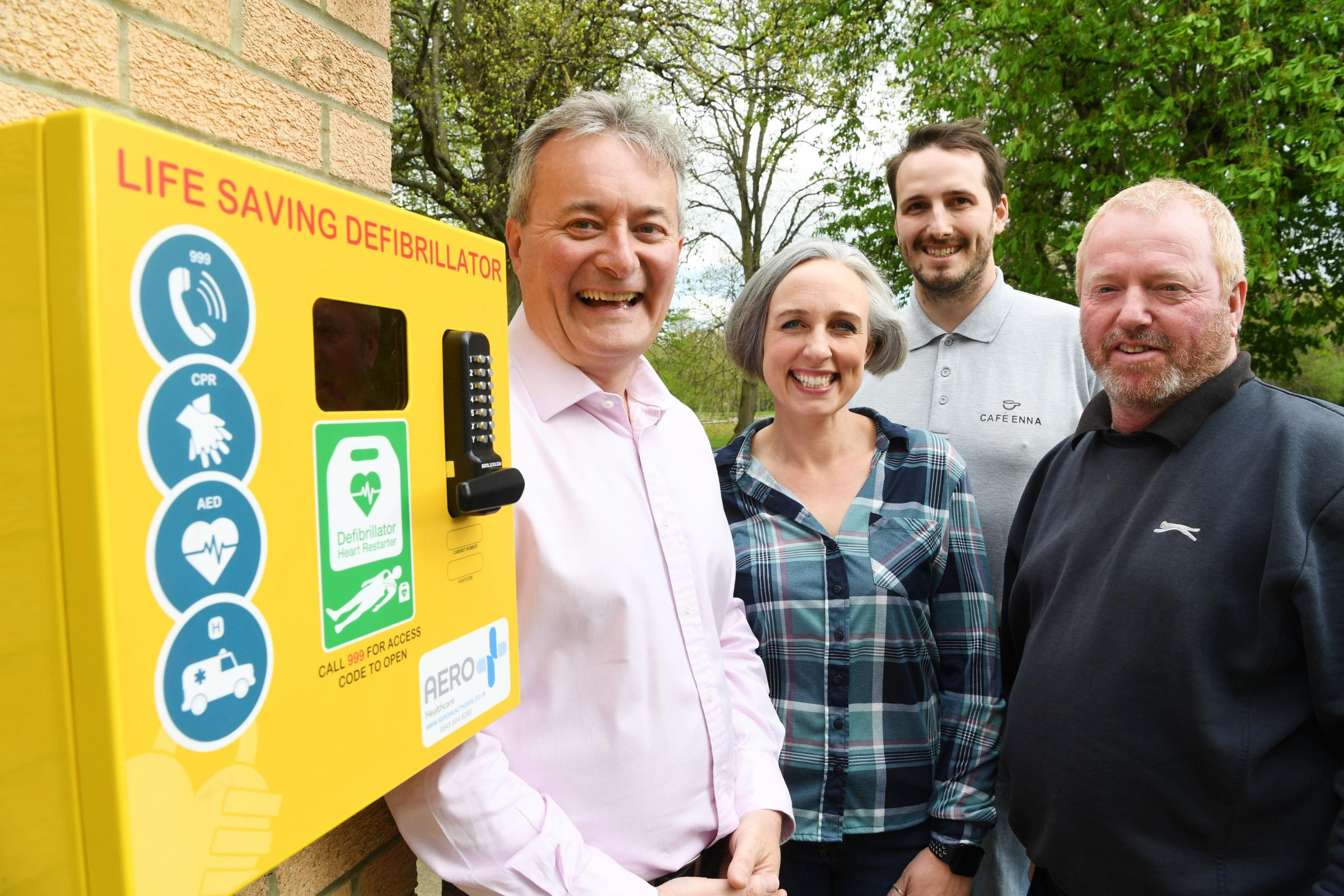 County councillor Derek Kennedy inspects the new defibrillator with Tyne Green parkrun director Claire Knowles, Cafe Enna representative Steve Plemper and Tynedale Golf Club chairman Brendan Murphy.
